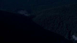 AX48_065_DFN - Aerial stock footage of Day for night color corrected aerial footage of a bird's eye of a river through evergreen forest in the Cascade Range, Washington