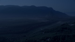 AX48_067_DFN - Aerial stock footage of 4K day for night color corrected aerial footage of a forest road through newer forest growth area near the Cascade Range, King County, Washington