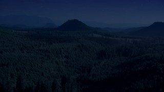 AX48_077_DFN - Aerial stock footage of Day for night color corrected aerial footage of evergreen forest, reveal a green hill and logging areas in King County, Washington