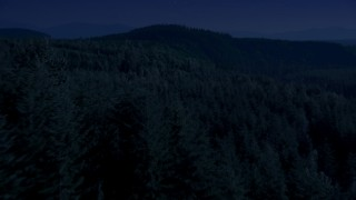 AX48_082_DFN - Aerial stock footage of Day for night color corrected aerial footage of a vast evergreen forest on a ridge in the Cascade Range, Washington
