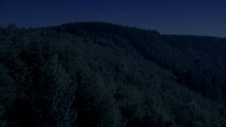 AX48_083_DFN - Aerial stock footage of 4K day for night color corrected aerial footage of flying over an evergreen forest and approach a mountain ridge in the Cascade Range, Washington