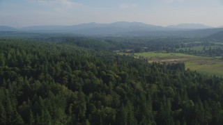 AX49_015 - 5K stock footage aerial video of flying by evergreen forest to reveal farm fields, Carnation, Washington