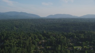 AX49_024 - 5K stock footage aerial video fly by evergreen forests, with partially hidden rural homes in the foreground, Sammamish, Washington