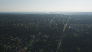 AX49_033 - 5K stock footage aerial video of flying over a suburban neighborhood crowded with trees toward Downtown Bellevue, Washington