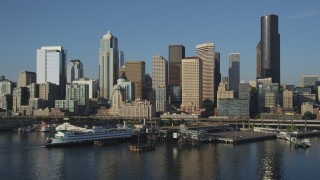 AX49_082 - 5K stock footage aerial video low flyby of Central Waterfront piers, ferry terminal, and Downtown Seattle skyline, Washington