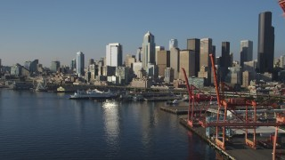 AX49_083 - 5K stock footage aerial video of the Central Waterfront and Downtown Seattle skyline, reveal cargo cranes, Washington