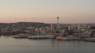 AX50_011 - 5K stock footage aerial video reverse view of the Seattle Space Needle and Central Waterfront piers at sunset, Downtown Seattle, Washington