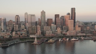 AX50_023 - 5K stock footage aerial video orbit Downtown Seattle skyscrapers, Alaskan Way Viaduct, and Central Waterfront piers in Washington, sunset