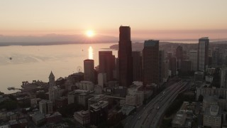 AX50_025 - 5K stock footage aerial video orbit Downtown Seattle skyscrapers at sunset in Washington, with Elliott Bay in the background