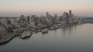 AX50_034 - 5K stock footage aerial video orbit the Space Needle, skyscrapers, and Central Waterfront piers in Downtown Seattle, Washington, sunset