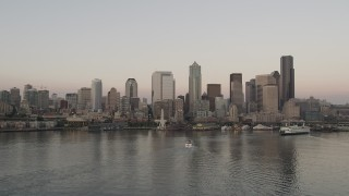 AX50_035 - 5K stock footage aerial video of the Central Waterfront and the Downtown Seattle skyline while flying by ferries sailing Elliott Bay, Washington, sunset