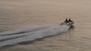AX50_038 - 5K stock footage aerial video of following a speedboat racing across Elliott Bay, Seattle, Washington, sunset
