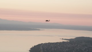 AX50_041 - 5K stock footage aerial video of tracking a helicopter over Puget Sound, Washington, sunset
