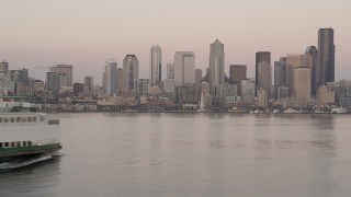 AX50_044 - 5K stock footage aerial video track a ferry sailing Elliott Bay and reveal the Downtown Seattle skyline in Washington, sunset