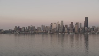 AX50_045 - 5K stock footage aerial video of view of the Downtown Seattle skyline from Elliott Bay, revealing a ferry sailing the bay, Washington, sunset