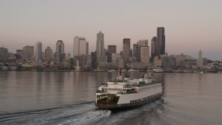 AX50_046 - 5K stock footage aerial video track a ferry sailing Elliott Bay and reveal the Central Waterfront and the Downtown Seattle skyline, Washington, sunset