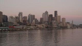 AX50_049 - 5K stock footage aerial video of low approach to the Great Wheel and Waterfront, and the towering skyline of Downtown Seattle, Washington, sunset