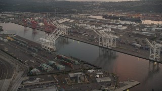 AX50_065 - 5K stock footage aerial video of cargo cranes by the Duwamish Waterway, Harbor Island, Seattle, Washington, sunset