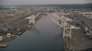 AX50_066 - 5K stock footage aerial video of passing cargo cranes by the Duwamish Waterway, Harbor Island, Seattle, Washington, sunset