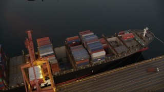 AX50_068 - 5K stock footage aerial video of flying over cargo ships laden with containers docked beneath cranes at the Port of Seattle, Washington, sunset
