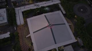 AX50_080 - 5K stock footage aerial video tilt to a bird's eye view of the KeyArena multi-purpose facility, Downtown Seattle, Washington, sunset