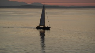 AX50_094 - 5K aerial stock footage video of sailboat on Elliott Bay at sunset, Seattle, Washington