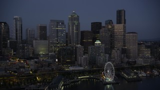 AX50_097 - 5K stock footage aerial video of approach the Seattle Waterfront and Downtown Seattle skyline at twilight, Washington