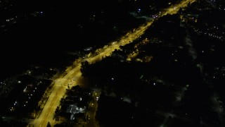 AX51_005 - 5K stock footage aerial video of bird's eye of a brightly-lit road through dark suburban neighborhoods, Rainier Beach, Seattle, Washington, night