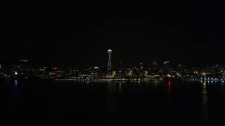 AX51_012 - 5K stock footage aerial video fly over Elliott Bay to approach Space Needle, Downtown Seattle, Washington, night