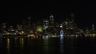 AX51_013 - 5K stock footage aerial video of low approach to Seattle Great Wheel and Waterfront, and Downtown Seattle skyline, Washington, night