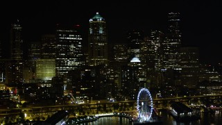 AX51_014 - 5K stock footage aerial video fly over Great Wheel and Central Waterfront to approach skyscrapers, Downtown Seattle, Washington, night