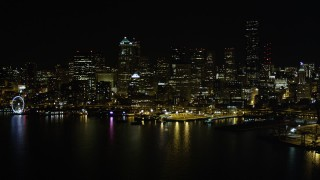 AX51_016 - 5K stock footage aerial video of Downtown Seattle skyline and Central Waterfront piers, Washington, night