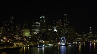 AX51_018 - Aerial stock footage of 5K aerial  video of the Seattle Great Wheel and Waterfront piers, and Downtown Seattle skyline in Washington, nighttime