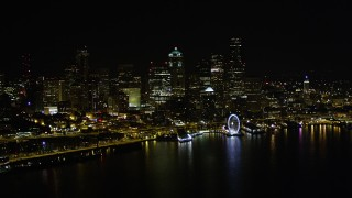 AX51_019 - 5K stock footage aerial video of the Downtown Seattle skyline, Seattle Great Wheel, and Central Waterfront piers, Washington, night