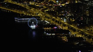 AX51_021 - 5K stock footage aerial video of Waterfront piers, approach Seattle Great Wheel, Downtown Seattle, Washington, night