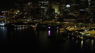 AX51_043 - 5K stock footage aerial video of Central Waterfront piers near Seattle Great Wheel in Downtown Seattle, Washington, night