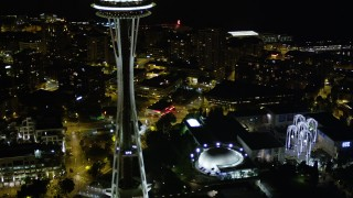 AX51_055 - 5K stock footage aerial video orbit Pacific Science Center and tilt to top of Space Needle, Downtown Seattle, Washington, night