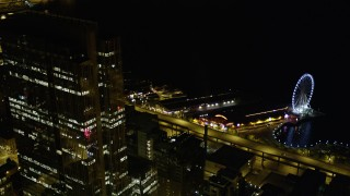 AX51_070 - 5K stock footage aerial video of Seattle Great Wheel and the Alaskan Way Viaduct at Central Waterfront, Downtown Seattle, Washington, night