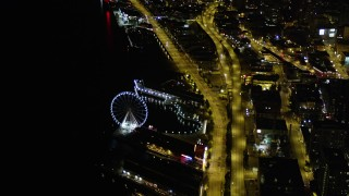 AX51_071 - 5K stock footage aerial video orbit the Seattle Great Wheel, Central Waterfront piers, and Alaskan Way Viaduct in Downtown Seattle, Washington, night