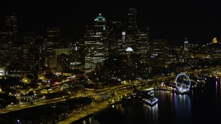 AX51_073 - 5K stock footage aerial video of reverse view of Downtown Seattle skyscrapers, reveal Central Waterfront, Washington, night