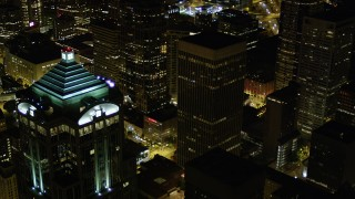 AX51_089 - 5K stock footage aerial video flyby 1201 3rd Avenue Tower to reveal base of Rainier Tower in Downtown Seattle, Washington, night