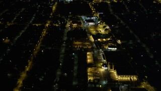 AX51_096 - 5K stock footage aerial video tilt from a strip mall to reveal neighborhoods at night in Rainier Valley, Seattle, Washington