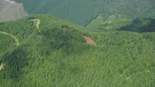 AX52_009 - 5K stock footage aerial video of reverse view of evergreen forest on a mountain peak in Thurston County, Washington