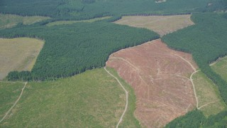 AX52_020 - 5K stock footage aerial video of reverse view of evergreen forests and clear cut logging areas, Lewis County, Washington