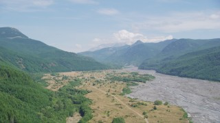 AX52_031 - 5K stock footage aerial video pass a wooded slope to reveal North Fork Toutle River leading to Mount St. Helens, Washington