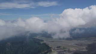 AX52_052 - 5K stock footage aerial video fly through clouds to reveal Mount Rainier in the far distance, Washington