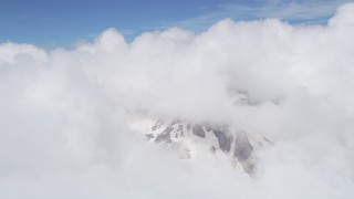 AX52_057 - 5K stock footage aerial video of snowy slopes of Mount St. Helens peeking through cloud coverage, Washington