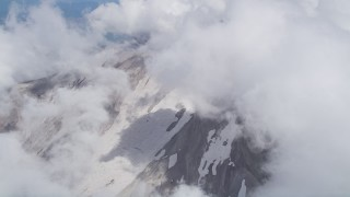 AX52_059 - 5K stock footage aerial video orbit thick clouds to reveal snow on Mount St. Helens' slopes, Washington