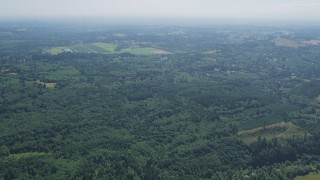 AX52_069 - 5K stock footage aerial video fly over evergreen forest to approach farm fields in La Center, Washington