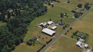 AX52_082 - 5K stock footage aerial video tilt to bird's eye view of farmhouse and barns beside country road in La Center, Washington